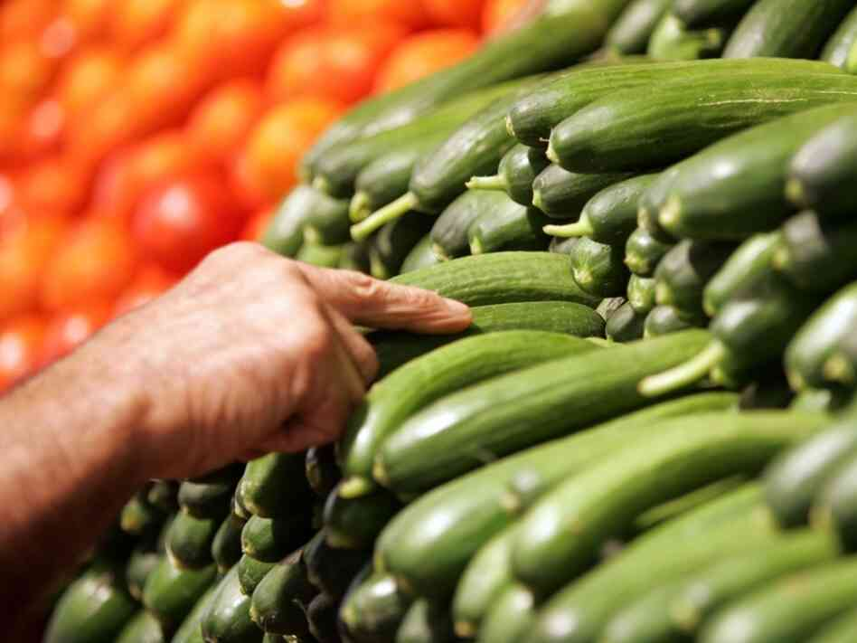 A worker fills the vegetable shelves with organic cucumbers at a supermarket.