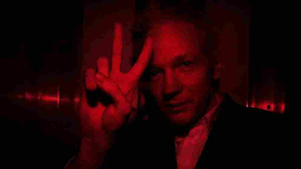Wikileaks founder Julian Assange gestures inside a prison van with red windows as he arrives at court on December 16, 2010.