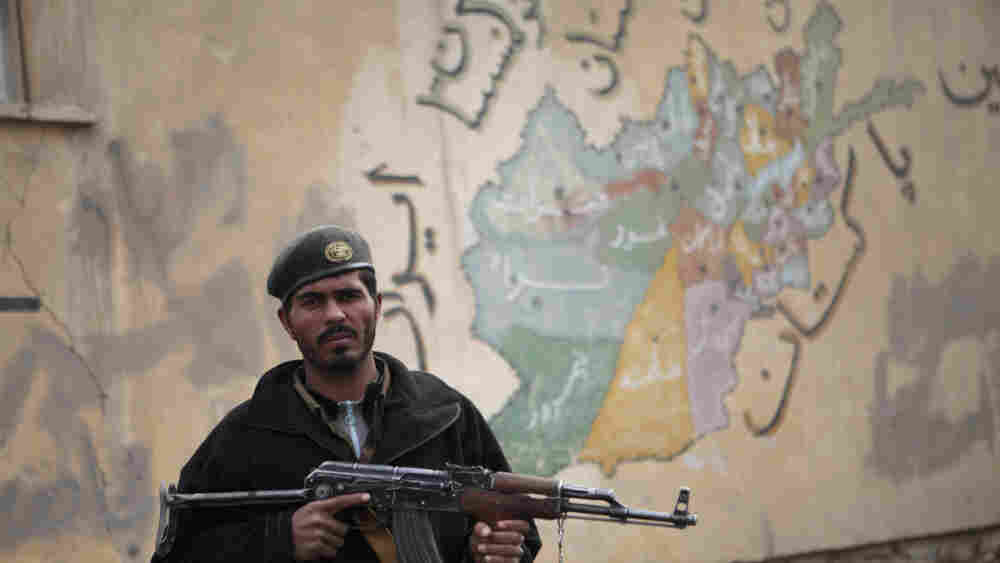 An Afghan National Army soldier stands in front of a mural depicting the map of Afghanistan.