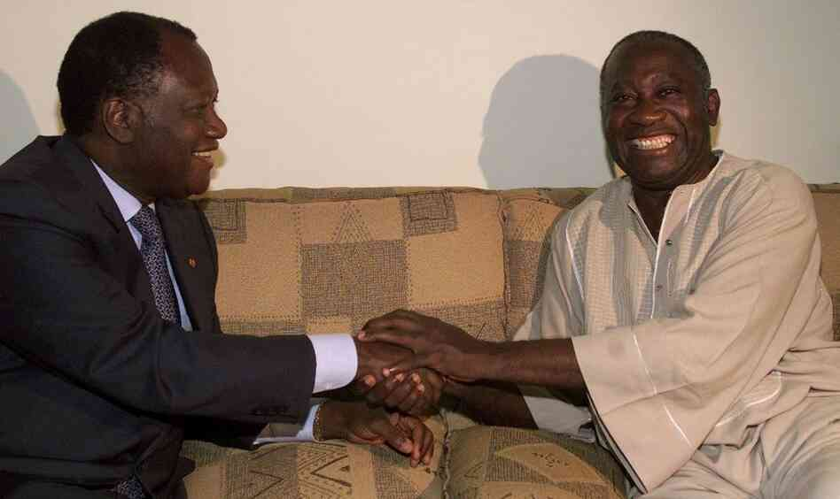 From Oct. 2000: Ivory Coast political rivals Alassane Ouattara, left, shakes hands with newly sworn-in Ivorian President Laurent Gbagbo in Abidjan.