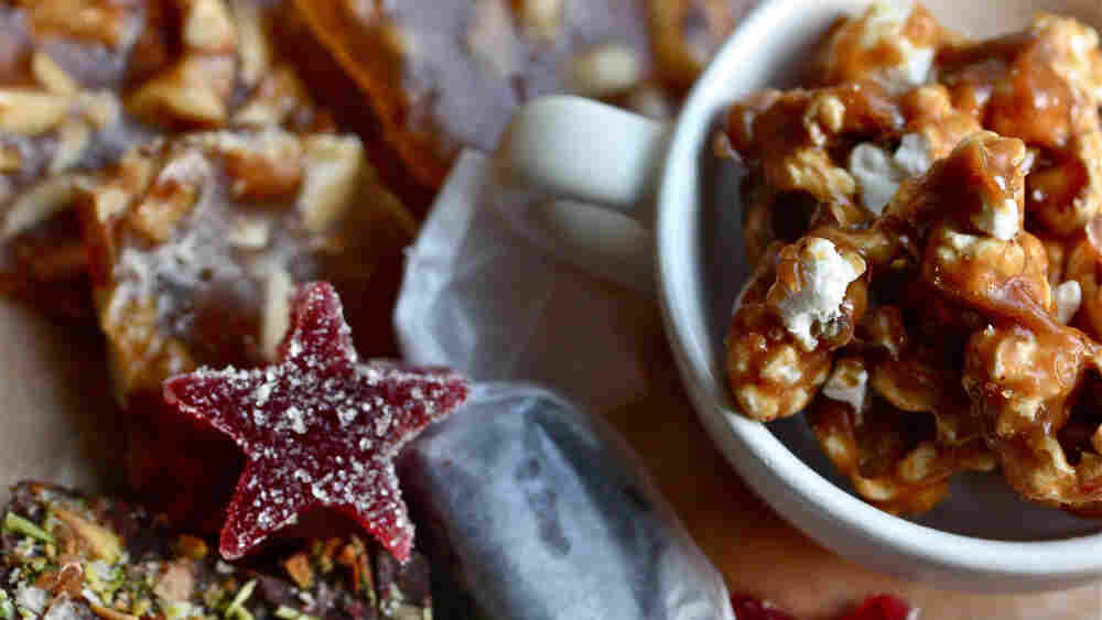 An assortment of homemade candies, including a sugared red jelly star, toffee, nut brittle, a caramel wrapped in parchment paper and a mug full of caramel corn.