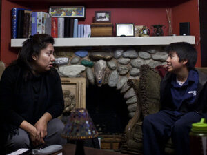 Yolanda Hilario and her teenage son Noel sit on the sofa in their home in South Central Los Angeles on Dec. 15.