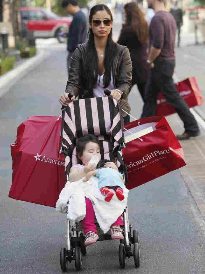 Monica Eaves, with her daughter, Sophia, 2, shops for holiday gifts at The Grove outdoor mall in Los Angeles on Tuesday.  A strong start to the holiday season is raising confidence that the consumer is back and that 2011 could be a better year for the economy than expected.