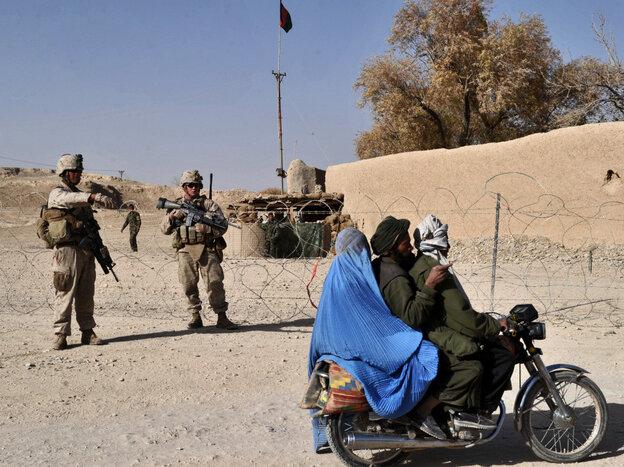 Motorcycle-riding Afghan villagers ride past U.S. Marines on patrol in Helmand province, Dec. 17, 2010.