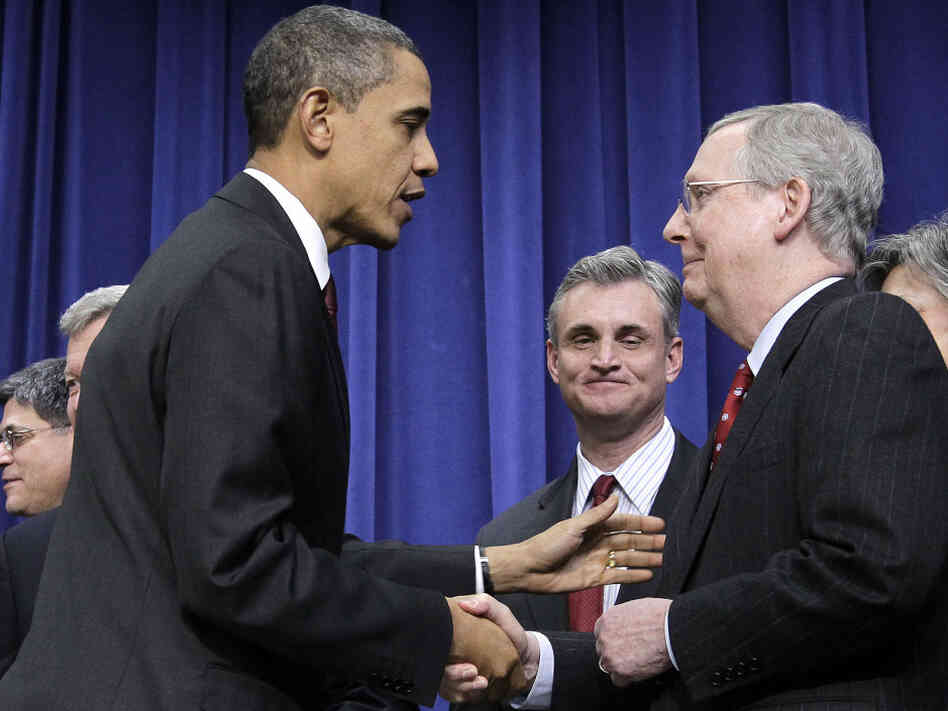 President Barack Obama, left, shakes hands with Senate Republican Leader Mitch McConnell, R-Ky., right, after signing the $858 billion tax deal into law in a ceremony in the Eisenhower Executive Office Building.