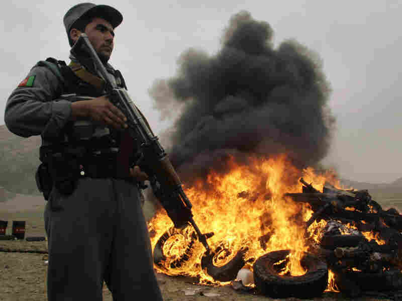 An Afghan policeman stands guard as flames rise up during a drug-burning ceremony in Herat, west of Kabul, Afghanistan, Feb. 21, 2010. Afghanistan is the world's largest producer of opium.