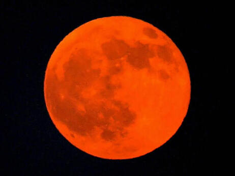 The moon appears red during a lunar eclipse in the Qatari capital of Doha, 28 August 2007. It's going to happen again tonight, and be visible across North America.