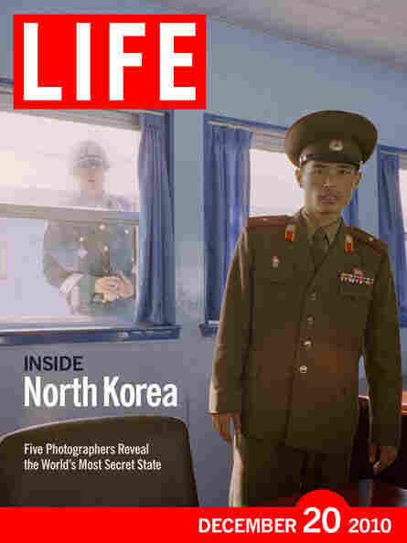 In a LIFE cover image, a South Korean soldier peers through a window at a North Korean counterpart at the volatile border between the two Koreas.