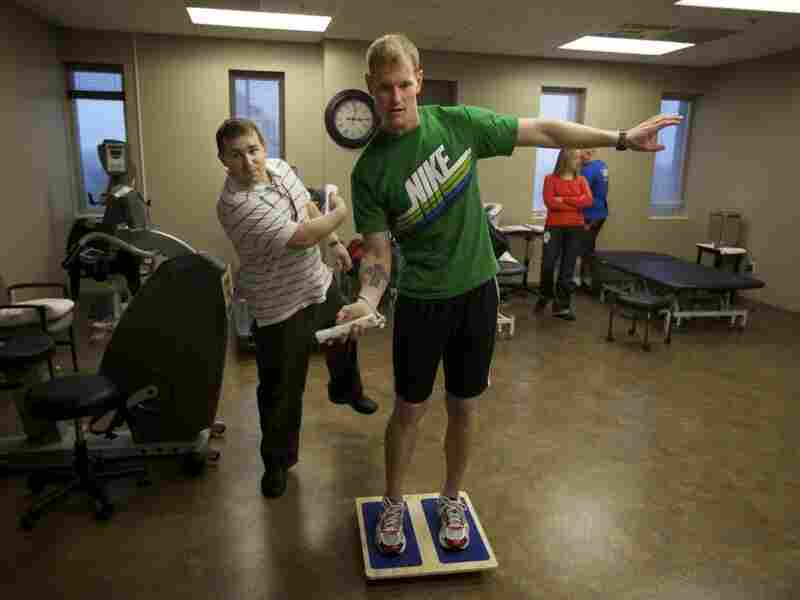 Brendan Jannesen, 23, plays Wii ping pong has part of his balancing therapy with physical therapist Brian Smith.