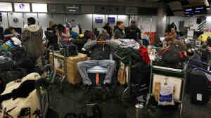 Passengers wait for flights in the check-in area of London's Terminal 3 at Heathrow Airport on Dec. 20, 2010.