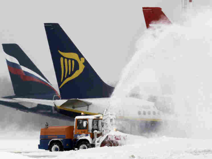 A snowblower clears snow from the airfield at Berlin's Schoenefeld airport. Germany's largest airport, in Frankfurt, has been forced to cancel hundreds of flights in recent days.