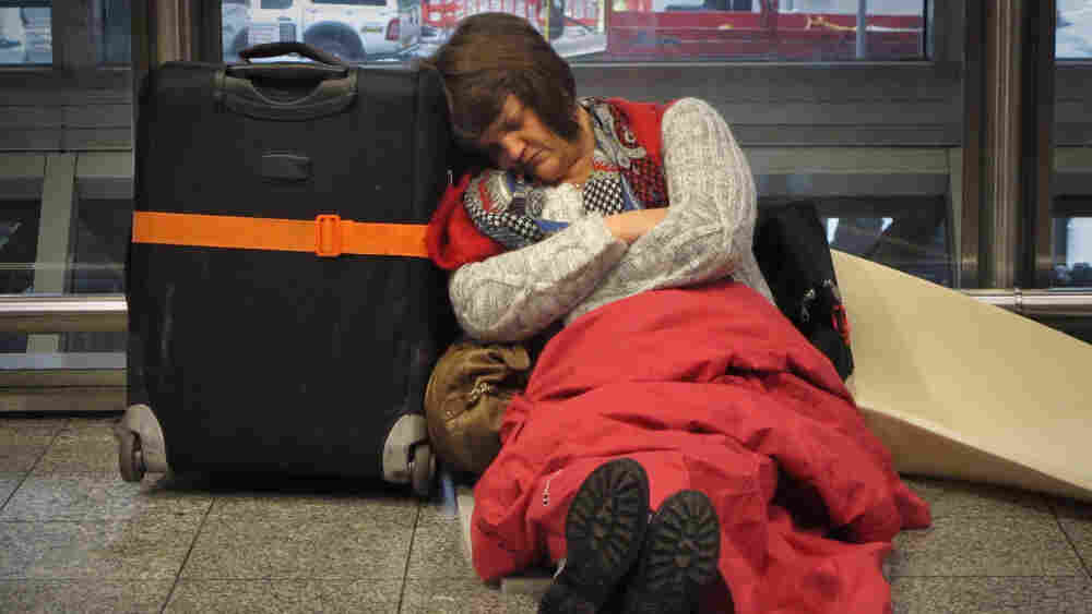 A passenger sleeps on the floor as she waits for a  flight from Terminal 3 at Heathrow airport Tuesday in London.