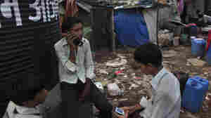 Boys in a Mumbai slum use their cell phones. There are vast stretches of India and elsewhere in the developing world with ample basic cellphone service, but that have yet to access social networking platforms like Facebook and Twitter.