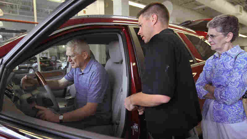 Bob and Carrol Welch learn about the features of the new Buick Enclave they purchased from Dave Weber (center), a delivery manager at a dealership in Lincolnwood, Ill. Even though General Motors turned a profit in 2010, its market share slipped.
