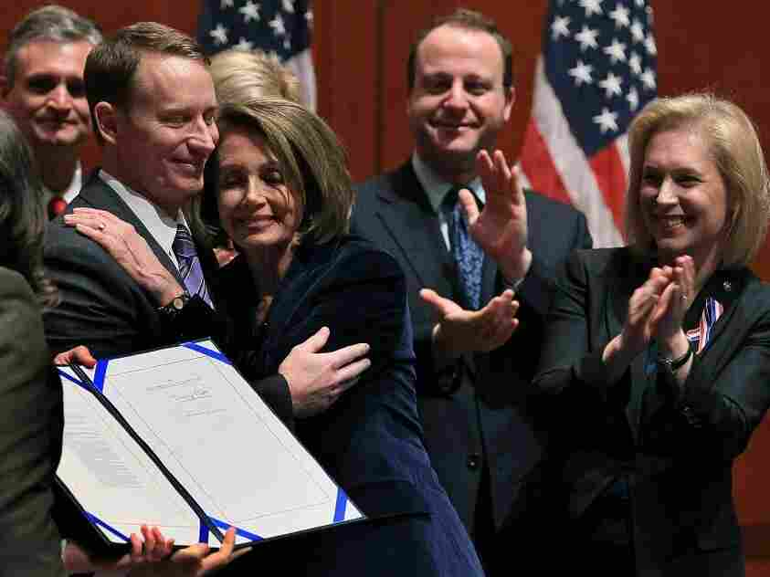"""Tuesday: Former U.S. Air Force Major Michael D. Almy (L) hugs House Speaker Nancy Pelosi, D-CA, after she signed legislation repealing """"don't ask, don't tell."""" It's now on the president's desk, awaiting his signature today."""