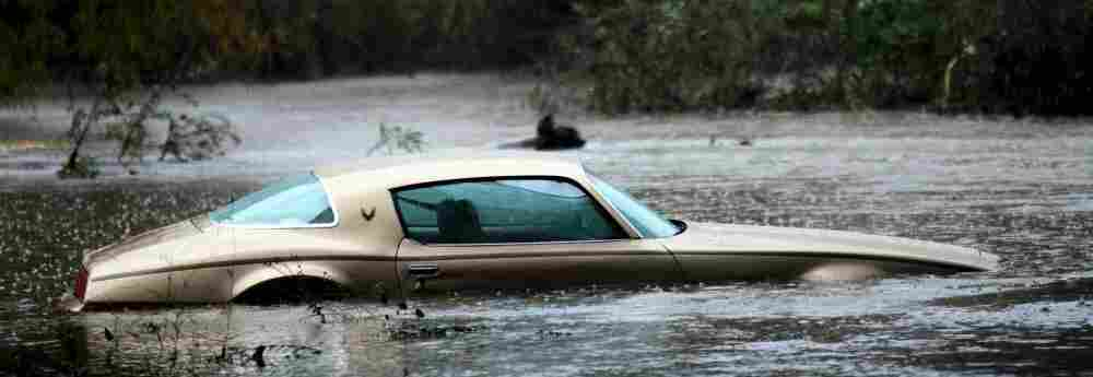 A vehicle sits partially submerged by flooding from the San Diego River during a powerful rainstorm on December 21, 2010.