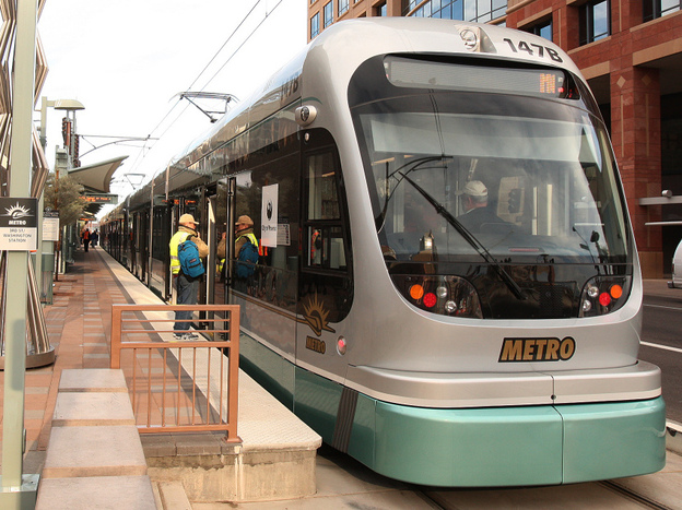 The first light rail car prepares to leave a station stop at the official opening of Metro Light Rail on Dec. 27, 2008, in Phoenix.  The 20-mile, $1.4 billion line runs from north-central Phoenix through downtown, and then east through suburban Tempe and Mesa.