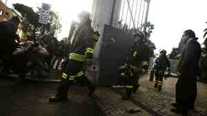 Italian firemen leave the Swiss embassy in Rome after a parcel bomb exploded, seriously injuring an employee.