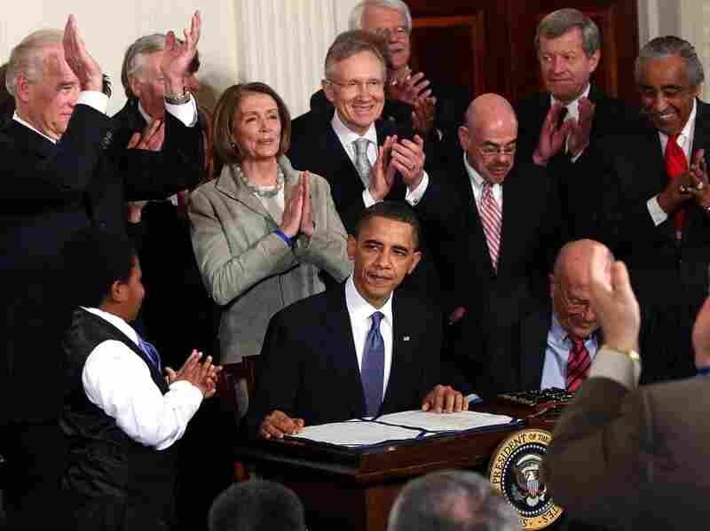 Lawmakers applaud President Obama after he signed the health care overhaul in March.