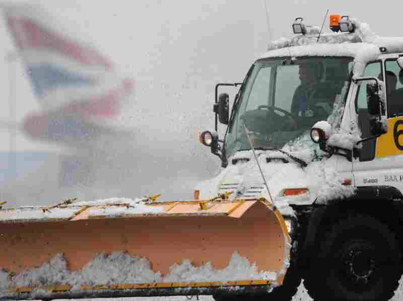 A snowploughattempts to clear a runway, at London's Heathrow Airport, London. Thousands of travelers have been stranded with planes unable to take off in the snow.