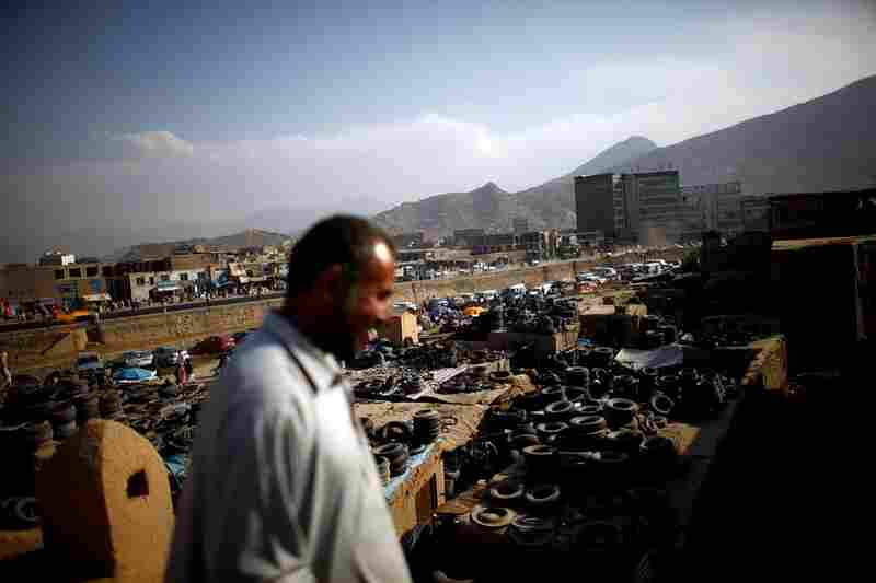 A man walks on the roof of a restored building in the Old City district. A sea of used tires stretches from the ancient quarter to the Kabul River. Many of the mud-walled houses in Murad Khane were buried under trash after 30 years of war and neglect.