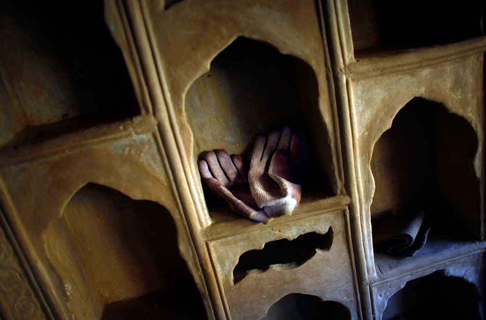Construction gloves rest on shelves of newly completed ornate plaster work in one of the homes in Murad Khane.