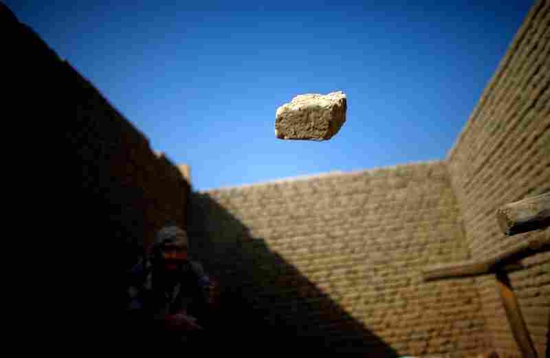 A worker throws an extra brick away from a newly constructed wall.