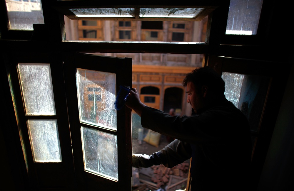 An Afghan window framer puts the finishing touches on a newly installed pane of glass. Emergency repairs to the quarter's private homes have made them structurally sound and weatherproof.