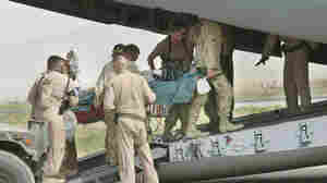 Army medics and soldiers carry a wounded soldier onto an Air Force C-17 at Bagram Air Field in this Aug. 8, 2002 photo. Members from the Aeromedical Evacuation Squadron at Bagram quickly reconfigure the hold of the massive cargo plane into a flying hospital that will take wounded troops from the war zone to American hospitals in Europe and the States.
