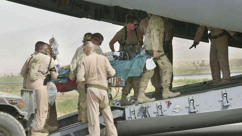 Army medics and soldiers carry a wounded soldier onto an Air Force C-17 at Bagram Air Field in this Aug. 8, 2002 photo. Members from the Aeromedical Evacuation Squadron at Bagram quickly reconfigure the hold of the massive cargo plan