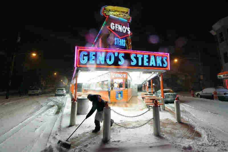 A man cleans the sidewalk in front of Geno's Steaks during the blizzard Sunday in Philadelphia.