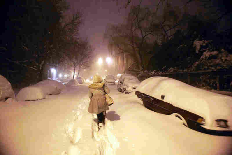 A woman walks through the snow in the early morning hours in Manhattan's East Village.