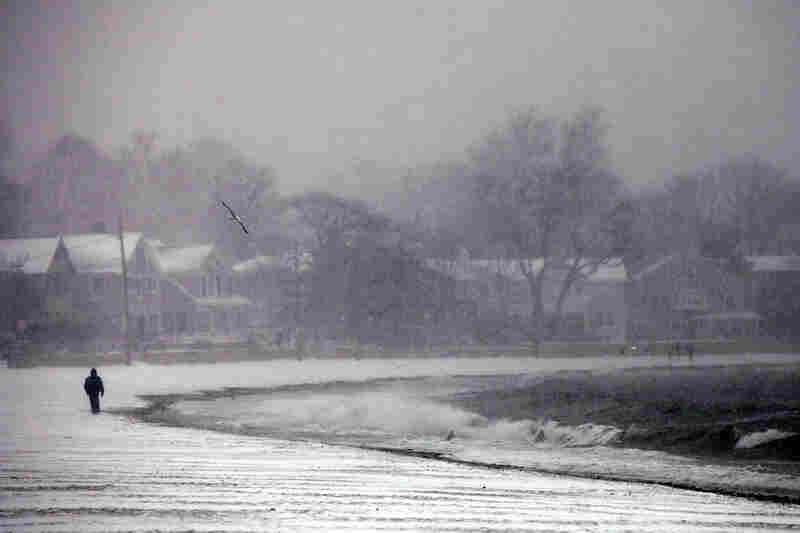 A man walks along a beach through the snowstorm Sunday in Westport, Conn.