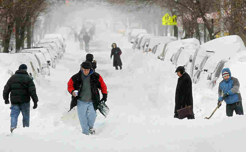 People walk through the snow in Manhattan's East Village in New York City. The tail end of a powerful storm across the Northeast snarled plans for millions of holiday travelers Monday, forcing airport closures and crippling road and rail traffic. The New York area was especially hard hit.