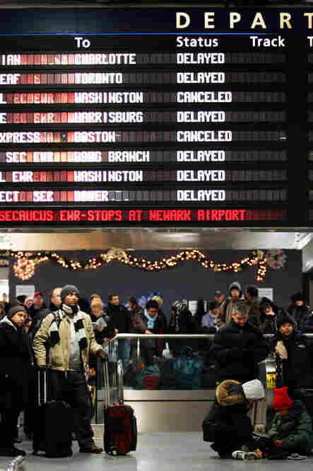 Travelers stranded by a severe winter storm wait at New York's Penn Station.