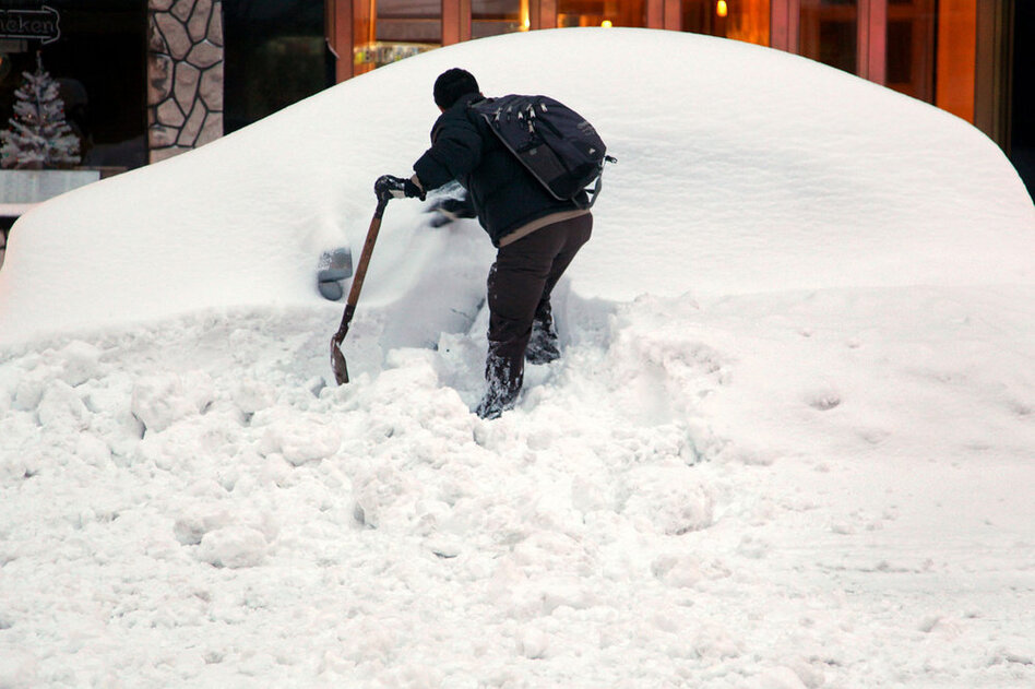 John Elliot of New York tries to dig out his rental car on a Manhattan street thanks in part to a good Samaritan who let him use a shovel.  (AP)