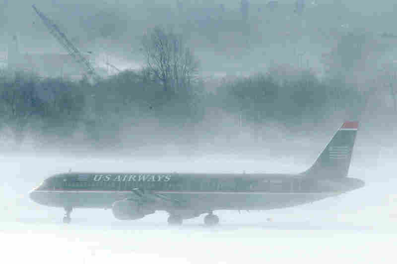 A U.S. Airways jet is blasted by snow on the tarmac at Philadelphia International Airport. The blizzard menaced would-be travelers by air, rail and highway, leaving thousands without a way to get home after the holidays and shutting down major airports and rail lines for a second day.