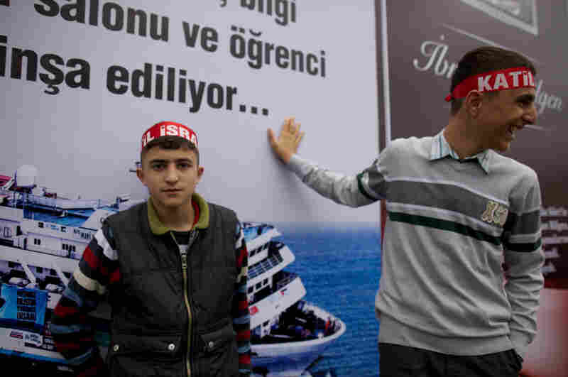 Youths at the rally marking the return of the Mavi Marmara wear headbands accusing Israel of murder in the deaths of nine activists aboard the ship in May.