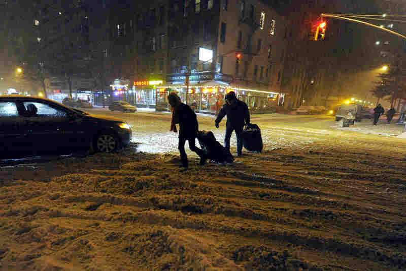 A couple crosses a snow-covered street on New York's Upper East Side.