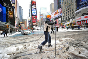 A man who gave his name as Marcus cross-country skis through snow in Times Square.