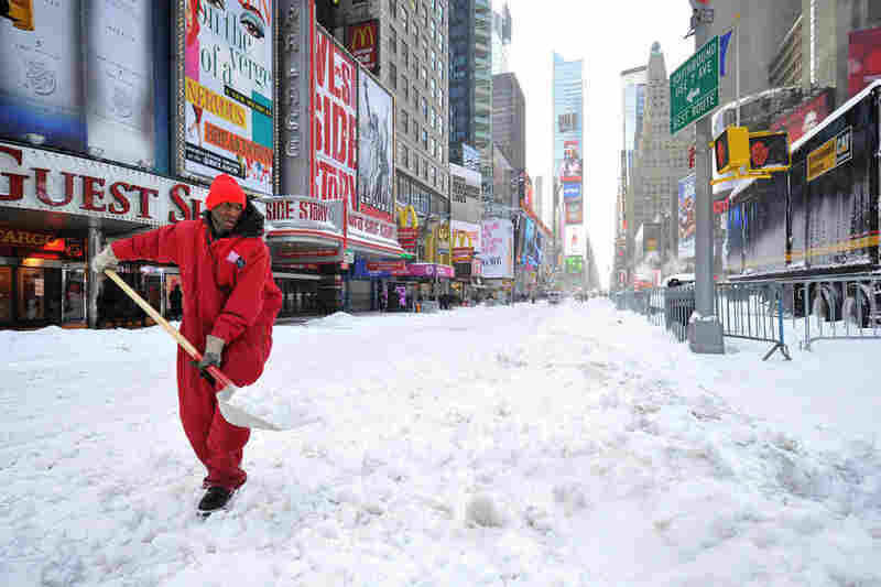 A worker shovels snow from Times Square on Monday morning.