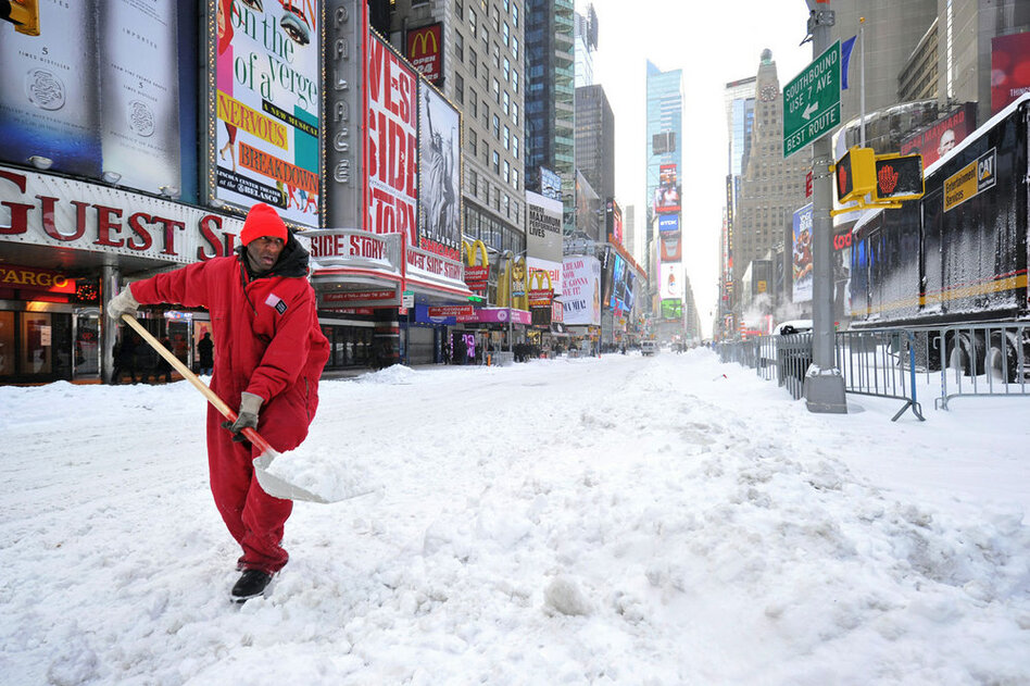 A worker shovels snow from Times Square on Monday morning.  (AFP/Getty Images)