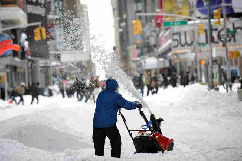 A man uses a snowblower to clear a street Monday in New York City's Times Square after a blizzard dropped 20 inches of snow in the area.