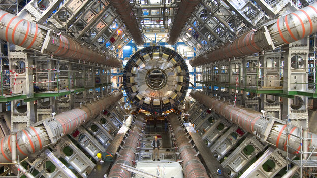 One of the goals of the ATLAS detector at the Large Hadron Collider is to search for the Higgs boson, a particle that scientists say gives everything in the universe mass. For scale, note the workers toward the bottom of the image.