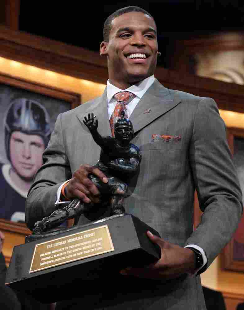 Auburn quarterbackCamNewtonpicks up the Heisman Trophy after his acceptance speech. Newton's father has been accused of trying tosolicit Mississippi State for money in exchange for his son's athletic service.