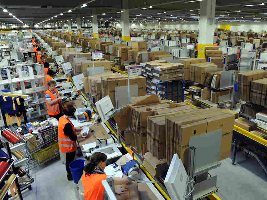 Employees pack boxes at a Amazon center in Germany.