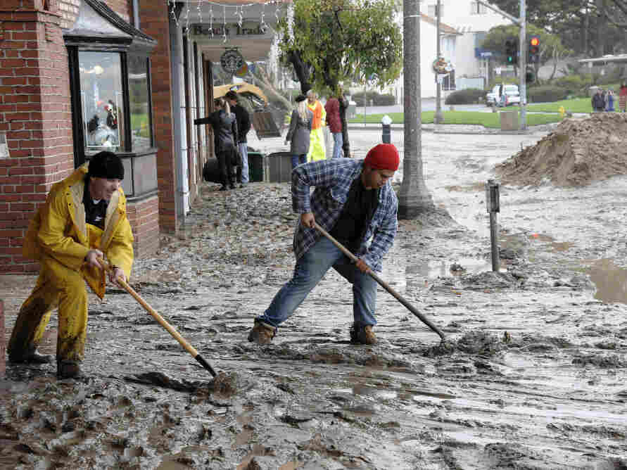Workers shovel mud out onto Pacific Coast Highway from the Laguna Cinemas in Laguna Beach, Calif.