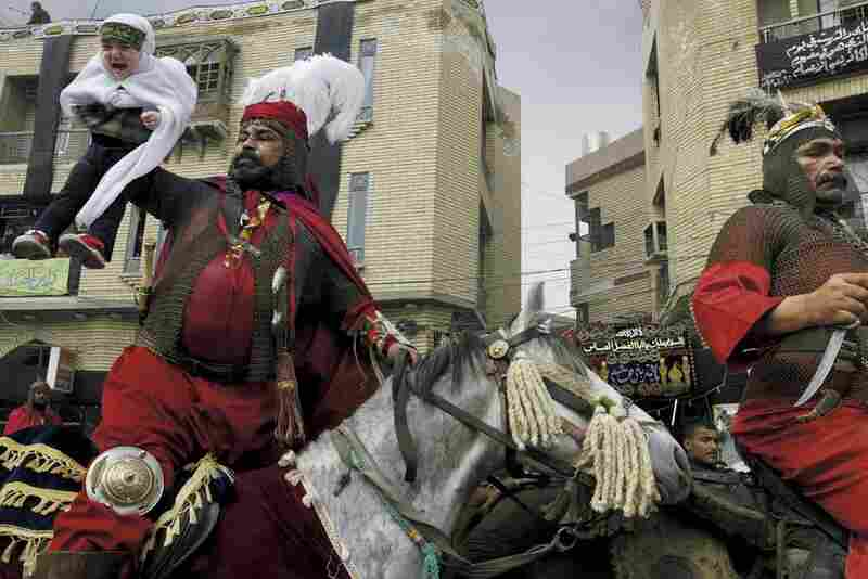 n Iraqi man dressed in ancient battle gear lifts a child during a procession through the streets of Kerbala. The men in red are playing the role of the killer of Imam Hussein, while the child is supposed to represent Hussein's child who was also killed. Kerbala, Iraq, 2004