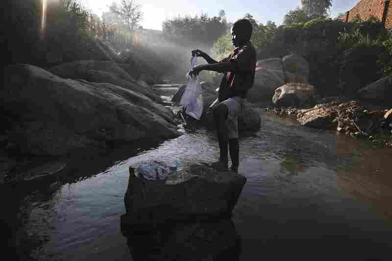 A child in this undated photograph washes clothes in a stream in Malawi.