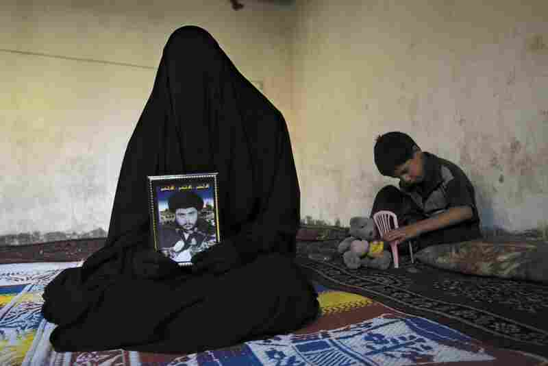 Ayam Mohamed, 19, a female combatant in Madhi Army who fought against U.S. soldiers, holds a portrait of Moqtada al Sadr during an interview with The New York Times at her home in Sadr city, 2004.